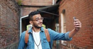 Radosny amerykanin afrykańskiego pochodzenia mężczyzna bierze selfie z smartphone kamerą outdoors zbiory