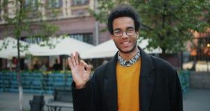 Radosny amerykanin afrykańskiego pochodzenia mężczyzna pokazuje OK gestowi uśmiechniętą pozycję w ulicie zdjęcie wideo