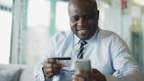 Radosny amerykanina afrykańskiego pochodzenia biznesmen utrzymuje kredytową kartę i smartphone w jego w formalnym odziewa płacić  zbiory
