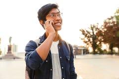 Radosny azjatykci męski uczeń opowiada smartphone w eyeglasses obrazy stock