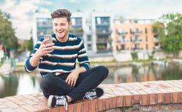 Radosny caucasian przystojny mężczyzna z ścierniskowym używa telefonem komórkowym fotografia royalty free