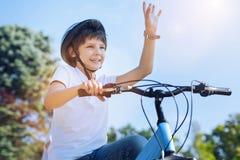 Radosny chłopiec powitanie somebody podczas gdy jadący bicykl obrazy royalty free