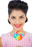 Radosny czarni włosy model trzyma barwionego lizaka Obrazy Stock