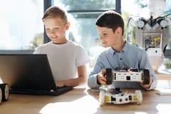 Radosny dzieciak ogląda jego przyjaciela program mechaniczny pojazd Zdjęcia Stock