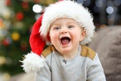 Radosny dziecko patrzeje kamerę w bożych narodzeniach w domu fotografia stock