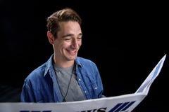 Radosny facet jest uśmiechnięty podczas gdy leafing przez nowej urzędówki fotografia royalty free