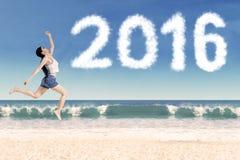 Radosny kobieta taniec przy wybrzeżem z liczbami 2016 obraz royalty free