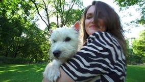 Radosny kobiety mienia zwierzęcia domowego pies w jej ręka zwrocie pod światłem słonecznym Handheld strza? zbiory wideo