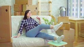 Radosny kobiety obsiadanie na leżance biorąc pod uwagę jego nowego nowożytnego mieszkanie i zbiory