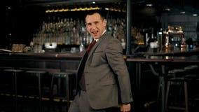 Radosny młody biznesmen świętuje sukces z jego rękami podnosić, tanczący i ono uśmiecha się podczas gdy patrzejący kamerę 4K zdjęcie wideo