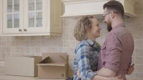 Radosny młody rodzinny obejmowanie w kuchni w ich nowym domu Szczęśliwa para rusza się nowy mieszkanie zbiory wideo
