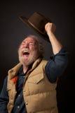 Radosny mężczyzna macha jego kapelusz w powietrzu Zdjęcia Stock