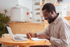 Radosny mężczyzna robi notatkom w dziennym planiście w kawiarni Fotografia Royalty Free