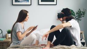 Radosny mężczyzna rusza się ręki na łóżku w domu w vr gogle gdy dziewczyna używa pastylkę zdjęcie wideo