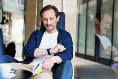 Radosny mężczyzna sprawdza czas na wristwatch obrazy royalty free
