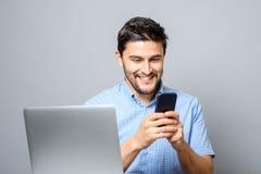 Radosny mężczyzna używa telefon komórkowego i obsiadanie przy stołem z laptopem Zdjęcia Stock