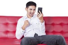 Radosny mężczyzna używa telefon komórkowego na leżance Fotografia Royalty Free