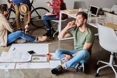 Radosny męski freelancer używa telefon dla komunikaci Fotografia Stock