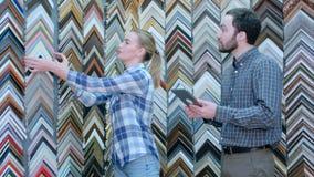 Radosny młoda kobieta pracownik opowiada z klientem o obrazek ramy szczegółach, używać cyfrową pastylkę Zdjęcia Royalty Free