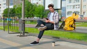Radosny młody człowiek czekać na transport przy przystankiem autobusowym ?awki samiec obsiadanie Facet używa smartphone słucha mu zdjęcie wideo