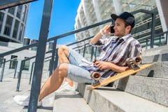 Radosny młody człowiek komunikuje na telefonie Fotografia Stock