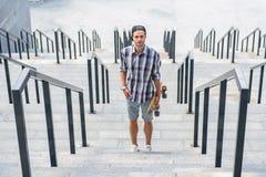 Radosny młody człowiek z deskorolka na krokach Fotografia Royalty Free