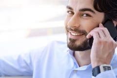Radosny męski pracownik opowiada na telefonie Obrazy Stock