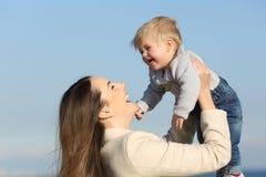 Radosny macierzysty bawić się podnoszący jej dziecko syna zdjęcia royalty free