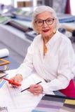 Radosny opłukujący modny bizneswoman jest ruchliwie z rysunkiem w biurze obrazy stock