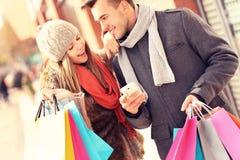 Radosny para zakupy w mieście z smartphone zdjęcia stock
