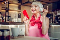 Radosny pozytyw starzejąca się kobieta cieszy się muzykę rockową obraz stock
