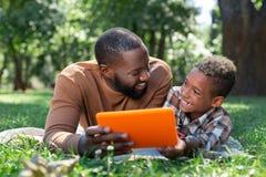 Radosny pozytywny ładny mężczyzna używa nowożytną technologię zdjęcia royalty free