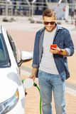 Radosny pozytywny mężczyzna tankuje jego samochód zdjęcie stock