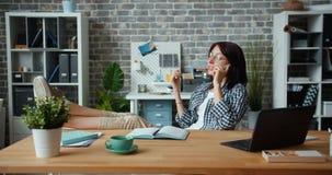 Radosny pracownika gawędzenie na telefonie komórkowym w biurowym obsiadaniu przy stołowy ono uśmiecha się zdjęcie wideo