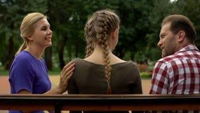 Radosny rodzinny opowiadać w parku, dyskutujący córka plany na przyszłość, wspiera ona zdjęcie royalty free