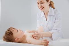 Radosny skupiający się pediatra robi setowi rozwijać ćwiczy Zdjęcie Royalty Free