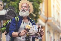 Radosny starszy męski podróżnik cieszy się spacer w miasteczku Zdjęcie Stock
