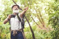 Radosny stary człowiek bierze fotografie w lesie Zdjęcia Stock