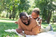 Radosny szczęśliwy ojciec i syn ma zabawę w parku wpólnie zdjęcie stock