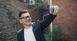 Radosny w średnim wieku mężczyzna bierze selfie z smartphone kamerą outdoors ono uśmiecha się zbiory wideo