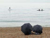 Radschaufel und Kajaks auf Meer mit zwei Regenschirmen im Vordergrund stockbild