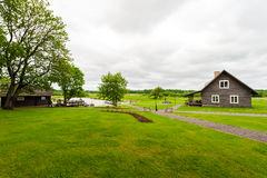 RADVILISKIS, LITHUANIA - JUNE 12, 2014: Unique Village and Rural Area in Lithuania with Wooden Building. Green grass and forest in Stock Image