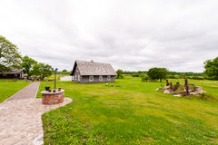 RADVILISKIS, LITHUANIA - JUNE 12, 2014: Unique Village and Rural Area in Lithuania with Wooden Building. Green grass and forest in Royalty Free Stock Photography