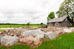 RADVILISKIS, LITHUANIE - 12 JUIN 2014 : Village unique et zone rurale en Lithuanie avec le bâtiment en bois Herbe verte et forêt  Photographie stock libre de droits