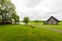 RADVILISKIS, LITHUANIE - 12 JUIN 2014 : Village unique et zone rurale en Lithuanie avec le bâtiment en bois Herbe verte et forêt  Image stock