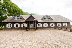 RADVILISKIS, LITUANIA - 12 DE JUNIO DE 2014: Pueblo único y zona rural en Lituania con el edificio de madera Hierba verde y bosqu Imágenes de archivo libres de regalías