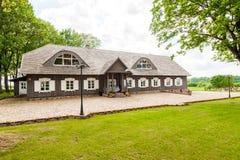 RADVILISKIS, LITUANIA - 12 DE JUNIO DE 2014: Pueblo único y zona rural en Lituania con el edificio de madera Hierba verde y bosqu Foto de archivo libre de regalías