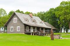 RADVILISKIS, LITUANIA - 12 DE JUNIO DE 2014: Pueblo único y zona rural en Lituania con el edificio de madera y la hierba verde Foto de archivo libre de regalías