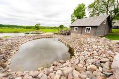 RADVILISKIS, LITUANIA - 12 GIUGNO 2014: Villaggio unico e zona rurale in Lituania con costruzione di legno Erba verde e lago in b fotografie stock