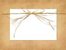 Raffia bow and a card tied on craft paper Royalty Free Stock Images